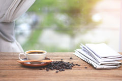Cup of coffee with coffee beam`s and newspapers, near the window Royalty Free Stock Images