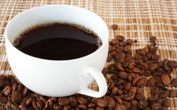 Cup of coffee with coffee beans. Cup of fresh brewed coffee with roasted coffee beans on straw placemat Stock Photo