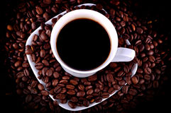 Cup of coffee in coffee beans Stock Photography