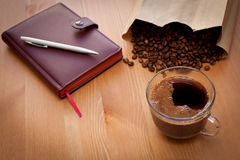 Cup of coffee and coffee beans. On wooden table royalty free stock photos