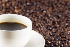 Cup of coffee and coffee beans background, warm toning, select Royalty Free Stock Image
