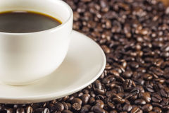 Cup of coffee and coffee beans background, warm toning, select Royalty Free Stock Photography