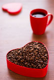 Cup of coffee and coffee beans in a box in the shape of a heart. Stock Photo