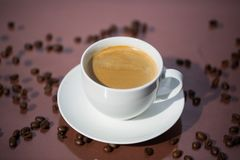 Cup of coffee with coffee beans on brown background Royalty Free Stock Images