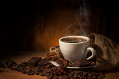 Cup of coffee in coffee beans on brown background. Cup of coffee with cinnamon, chocolate and anise in coffee beans on wooden brown background and burlap bag Stock Photo