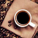 Cup of coffee with coffee beans on  brown napkin on wooden backg Stock Photography
