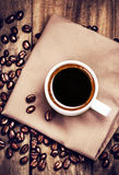 Cup of coffee with coffee beans on  brown napkin on wooden table Stock Image