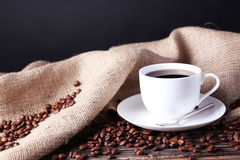 Cup of coffee with coffee beans on brown wooden background. Royalty Free Stock Photo