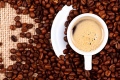 Cup of coffee on coffee beans and burlap Royalty Free Stock Photos