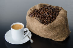 A cup of coffee with coffee beans in a burlap bag Royalty Free Stock Photography