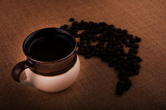 Cup of coffee with coffee beans on a burlap sack Royalty Free Stock Photography