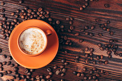 Cup of coffee with coffee beans. Ceramic orange cup of coffee with foam and coffee beans, lying on wooden table Stock Photography