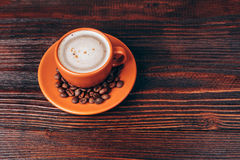 Cup of coffee with coffee beans. Ceramic orange cup of coffee with foam and coffee beans, standing on wooden table Stock Image