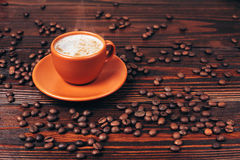 Cup of coffee with coffee beans. Ceramic orange cup of hot coffee with foam and coffee beans, standing on wooden table Royalty Free Stock Image