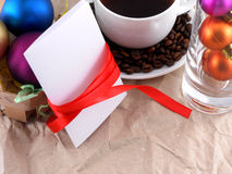 Cup of coffee with coffee beans, christmas balls and invitation card Royalty Free Stock Images