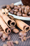 A cup of coffee with coffee beans and cinnamon sticks. Close up Stock Photos
