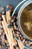 A cup of coffee with coffee beans and cinnamon sticks. Close up Royalty Free Stock Image