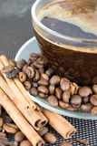 A cup of coffee with coffee beans and cinnamon sticks. Close up Stock Photo