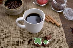 A cup of coffee, coffee beans, cinnamon sticks, a sweet chocolate ingredient in a jar. A cup of coffee, coffee beans, cinnamon sticks, a sweet chocolate Royalty Free Stock Image