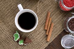 A cup of coffee, coffee beans, cinnamon sticks, a sweet chocolate ingredient in a jar. A cup of coffee, coffee beans, cinnamon sticks, a sweet chocolate Stock Photos