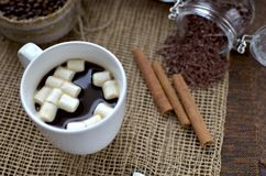 A cup of coffee, coffee beans, cinnamon sticks, a sweet chocolate ingredient in a jar. A cup of coffee, coffee beans, cinnamon sticks, a sweet chocolate Stock Photo