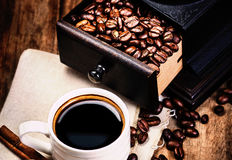 Cup of coffee with coffee beans and Coffee grinder on wooden bro Stock Image