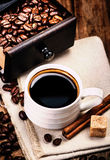 Cup of coffee with coffee beans and Coffee grinder on wooden bro Royalty Free Stock Photo