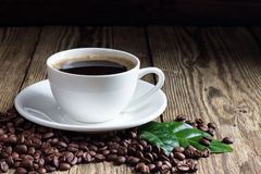 Cup of coffee with coffee beans. On wooden background royalty free stock photography