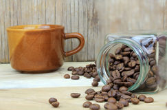 Cup of coffee and coffee beans in glass bottle. On wood Royalty Free Stock Image