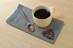 Cup of coffee with coffee beans on gray napkin Royalty Free Stock Image