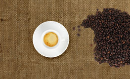 Cup of coffee with coffee beans on jute fabric Stock Photo