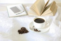 A cup of coffee, coffee beans laid out in the shape of a heart, behind an open book, notebook, mobile phone, pen on a. White background. Horizontal. Daylight Stock Photo