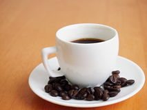 Cup of Coffee and Coffee beans. Cup of Coffee with Coffee beans laying around royalty free stock photo