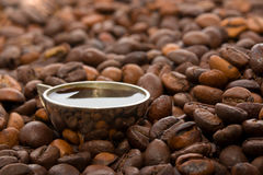 A cup of coffee among coffee beans Royalty Free Stock Photo
