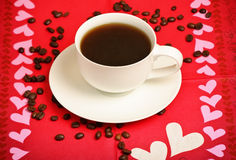 Cup of coffee with coffee beans and napkin Royalty Free Stock Images