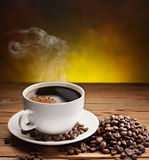 Cup of coffee with coffee beans near it. Royalty Free Stock Photos