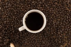 Cup of coffee and coffee beans on old wooden background Royalty Free Stock Photo