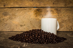 Cup of coffee of coffee beans on the old wooden floor. Stock Image