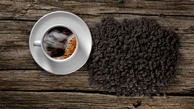 Cup of coffee and coffee beans on an old wooden table. 3D Rendering Royalty Free Stock Image