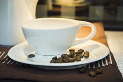 Cup of coffee with coffee beans on plate Royalty Free Stock Images