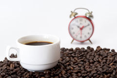 Cup of coffee on coffee beans. And red alarm clock Stock Image