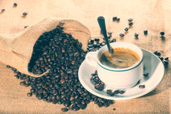Cup of coffee and coffee beans in sack Stock Image