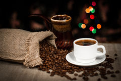 Cup of coffee and coffee beans scattered on table, still life with bokeh effect Royalty Free Stock Image