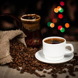 Cup of coffee and coffee beans scattered on table, still life with bokeh effect. Coffee cup and coffee beans spilled out of sack, still life with bokeh effect Stock Image