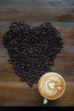 Cup of Coffee and Coffee Beans Shaped like a Heart Stock Photo