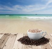 Cup of coffee with coffee beans on table. With sea Stock Photos