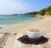 Cup of coffee with coffee beans on table. With sea Royalty Free Stock Photography