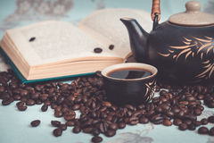 Cup of coffee, coffee beans, teapot, open book Royalty Free Stock Photography