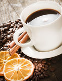 Cup of coffee and coffee beans, warm lighting. Royalty Free Stock Photo