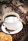 Cup of coffee and coffee beans, warm lighting. Royalty Free Stock Photos